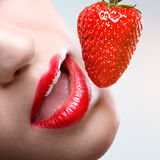 Female red lips, eating strawberries Stock Images