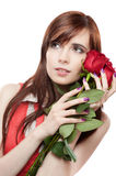 Female with red roses on white background. Vertical portrait of young attractive red-gaired caucasian female soft looking off camera and gently smiling while stock photo