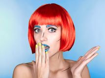 Female in red wig and in comic pop art make-up style on blue ba. Portrait of young woman in comic pop art make-up style. Female in red wig on blue background Stock Photos
