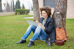 Female redhead art student drawing outdoors Stock Images