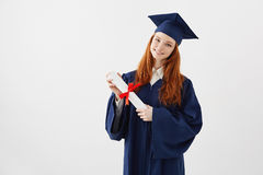 Female redhead graduate student with diploma smiling looking at camera. Copyspace. Royalty Free Stock Images