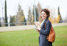 Female redhead student carrying notebook and coffee to go Royalty Free Stock Photos