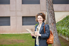 Female redhead student carrying notebook and coffee to go Royalty Free Stock Images
