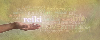 Female Reiki Healer with Healing Word Cloud. Woman's hand, open with the word 'REIKI' floating above, surrounded by a relevant healing related word cloud on a Royalty Free Stock Photography