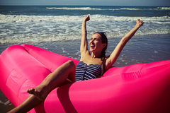 A female rejoicing on a deep-rosy air rubber boat upping her han. A dame rejoicing and smiling on a deep-rosy air rubber boat upping her hands wearing blue Stock Photography