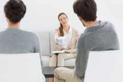 Female relationship counselor in meeting with young couple. In her office royalty free stock photography