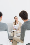 Female relationship counselor in meeting with young couple Royalty Free Stock Photos