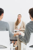 Female relationship counselor in meeting with young couple. In her office stock images