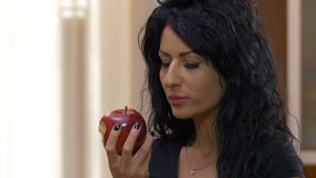 Female relaxing at home while eating a red delicious apple enjoying healthy nutrition. Attractive female relaxing at home while eating a red delicious apple stock video footage