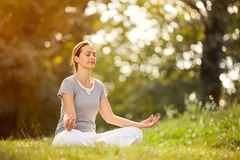 Female relaxing in yoga pose in green nature royalty free stock image