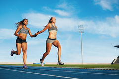Female relay racing team on racetrack Royalty Free Stock Photos