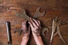 Female repairer woman hands spanner tools feminism. Female repairer. Woman hand holding a spanner and other tools lay on a wooden background. Feminism and Stock Photo