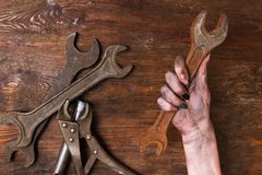 Female repairer woman hands spanner tools feminism. Female repairer. Woman hand holding a spanner and other tools lay on a wooden background. Feminism and Stock Images