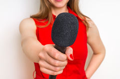 Female reporter with black microphone making interview. Journalism and broadcasting concept Stock Photos