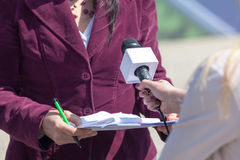 Female reporter holding microphone, interviewing woman. Female journalist holding mic, interviewing woman Stock Image