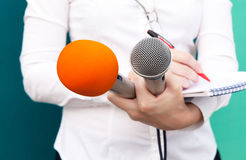Female reporter or journalist at press conference. Female reporter or journalist at news conference, writing notes, holding microphones Royalty Free Stock Image