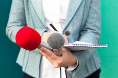 Female reporter or journalist at press conference, writing notes Royalty Free Stock Images