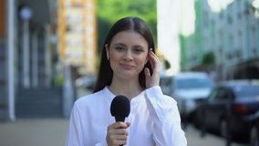 Female reporter with microphone in headphones talking at camera, live daily news