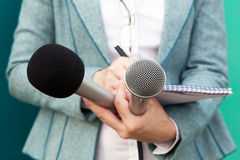 Female reporter at press conference, writing notes, holding microphones Royalty Free Stock Photos