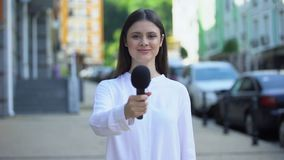 Female reporter proposing microphone, taking interview on street, daily news
