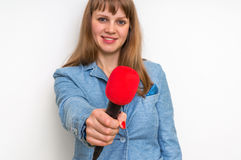 Female reporter with red microphone making interview. Journalism and broadcasting concept Stock Images