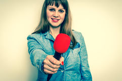 Female reporter with red microphone making interview Royalty Free Stock Photos