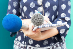 Female reporter taking notes at news conference Royalty Free Stock Photography