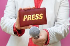Female journalist at work. Female reporter at work, holding microphone and press card royalty free stock image