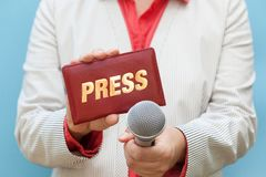 Female journalist at work. Female reporter at work, holding microphone and press card stock image