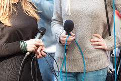 Female reporters holding microphones waiting for news conference. Female journalists holding microphones waiting for press conference Stock Photo