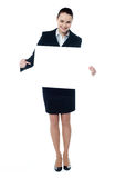 Female representative of a company. Female representative pointing towards placard, smiling at camera Stock Photo