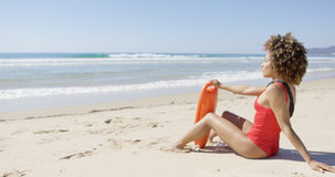 Female with rescue float sitting on beach Stock Images