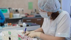 Female research assistant in white lab coat, protective mask, cap and gloves sitting in medical laboratory and working. Female research assistant dressed in stock video
