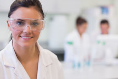 Female researcher with colleagues in background at lab Stock Image