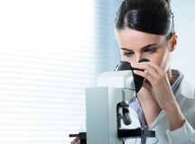 Female researcher using microscope close up Royalty Free Stock Images