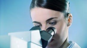 Female researcher using microscope close up Stock Photo