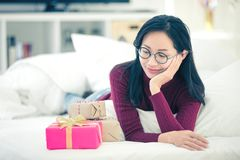 Female rest on bed and looking gift box with smile face royalty free stock photo