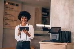 Female restaurant manager with a digital tablet. Portrait of female manager in restaurant with digital tablet. Beautiful young african business woman in royalty free stock photo