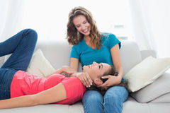 Female resting on friends lap in the living room Stock Photography