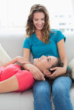 Female resting on friends lap in the living room Royalty Free Stock Image
