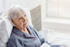 Female retiree lying in bright apartment of clinic Royalty Free Stock Images