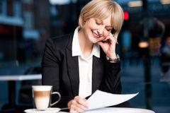 Female reviewing business report in cafe. Attractive business lady reviewing business document Royalty Free Stock Image