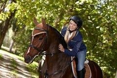 Female rider caressing horse stock photo