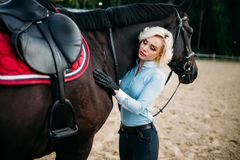 Female rider hugs her horse, horseback riding Royalty Free Stock Image
