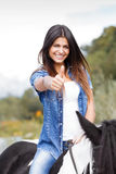 Female rider sitting on her horse in ok gesture. Portrait of attractive brunette female rider sitting on her horse in ok gesture Royalty Free Stock Images