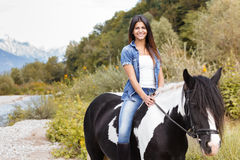 Female rider sitting on her horse and smiling. Attractive brunette female rider sitting on her horse and smiling Stock Photography