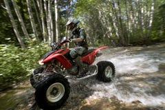 Female riding ATV through creek