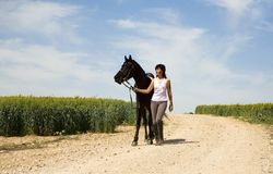 A female riding on a black horse Royalty Free Stock Photography