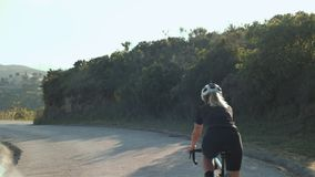 Female road cyclist in the sunset stock video