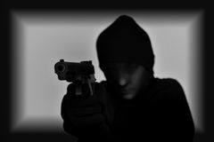Female robber holding a gun Stock Photo
